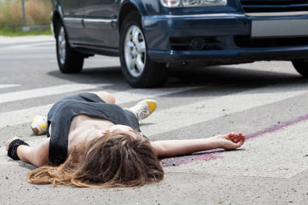 unconscious: Dead woman lying on a street after road accident
