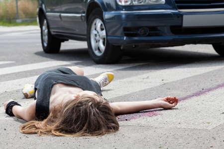 vermoord: Dode vrouw liggend op een straat na verkeersongeval Stockfoto