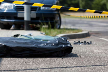 Corpse in plastic bag after car accident, horizontal