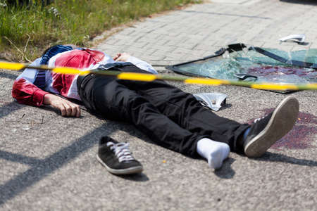 Voorzichtigheid tape en dode man liggend op de straat, horizontale Stockfoto