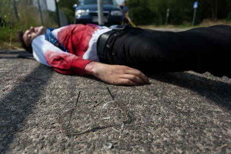 Dead man in bloody shirt lying on the street