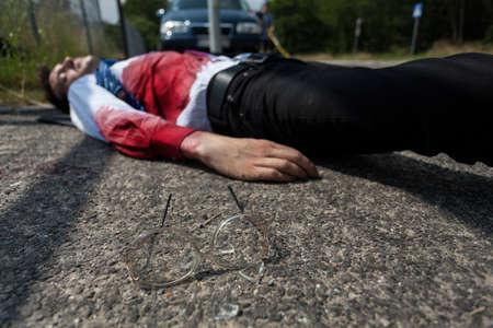 hemorragias: Hombre muerto en camisa ensangrentada tirado en la calle Foto de archivo