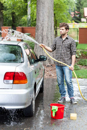 Man cleaning his car in front of house photo