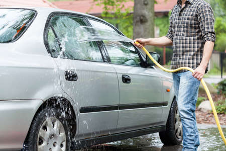 rinse: View of man rinsing foam from car Stock Photo
