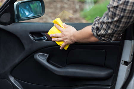 Man cleaning door in a car, horizontal photo