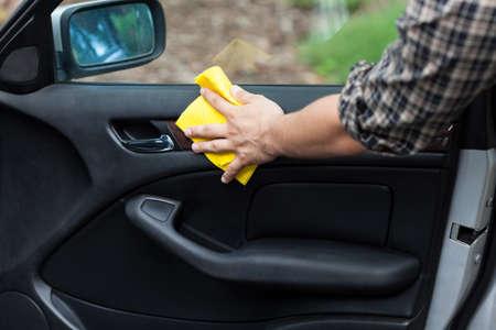 clean street: Man cleaning door in a car, horizontal