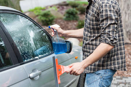 car glass: Man cleaning window in a car Stock Photo