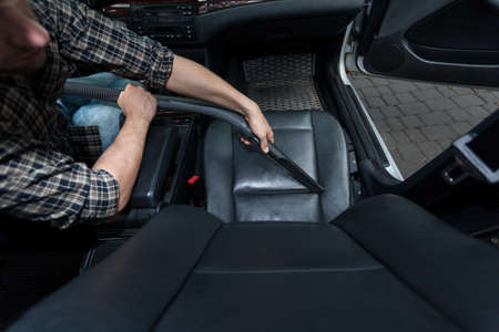 hoover: Horizontal view of man dusting cars chair