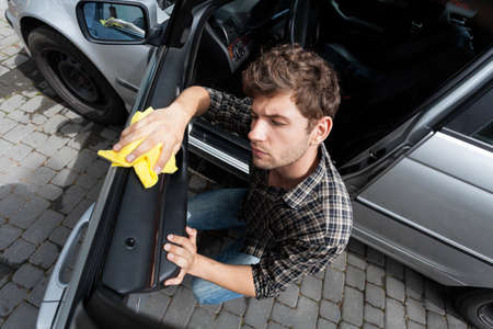 Horizontal view of man cleaning a car photo