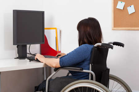 everyday jobs: Woman on wheelchair working in the office Stock Photo