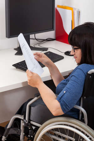disability insurance: Disabled woman with documents in the office