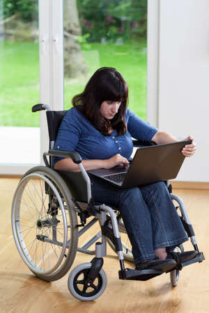 disability insurance: Vertical view of disabled woman using laptop