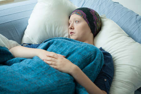 Sad woman with cancer lying in bed photo