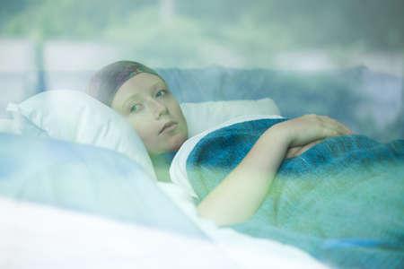 암을 앓고 침대에서 젊은 여자 스톡 콘텐츠