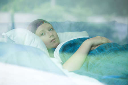 Young woman in bed suffering from cancer Stock Photo