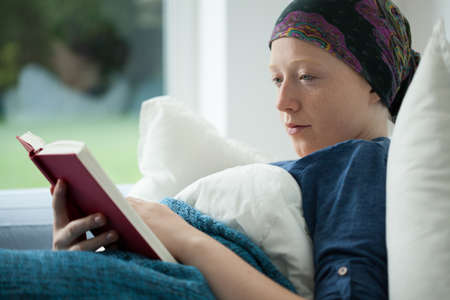 Woman with cancer reading a book in bed