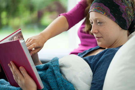 Girl with cancer holding photo album, horizontal