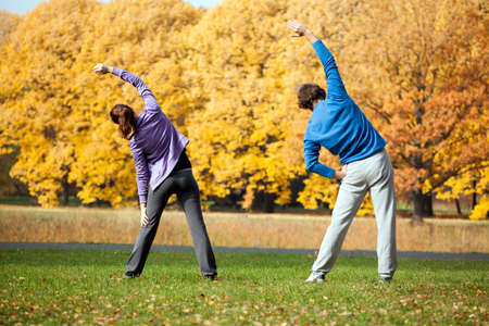 Young couple training in the park in sunny day photo