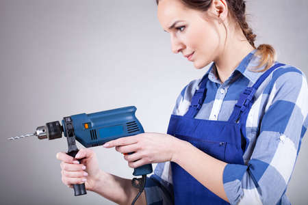 handywoman: Beautiful handywoman in blue uniform working with drill Stock Photo
