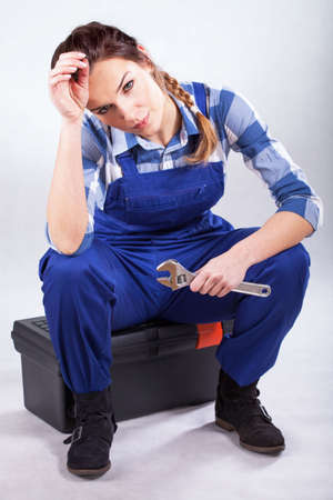 Beautiful handywoman sitting on toolbox with wrench