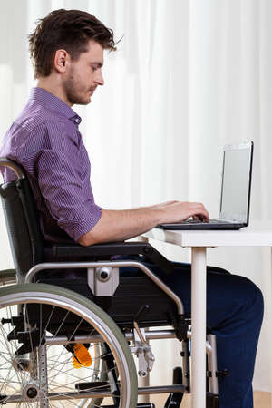 health care worker: Young disabled man surfing on the Internet at home