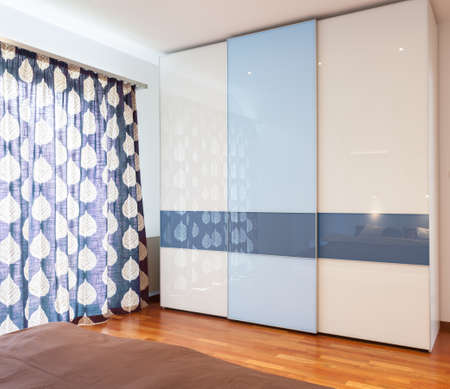 View of blue and white wardrobe in bedroom