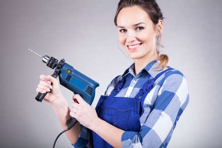 handywoman: Beautiful young handywoman with drill standing and smiling