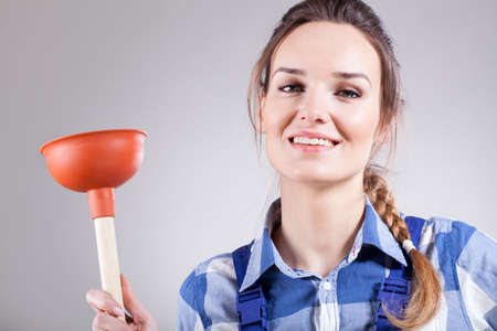 handywoman: Funny picture of young handywoman with plunger