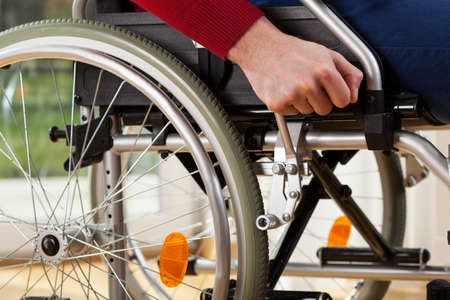 breaks: Close-up of disabled man using wheelchair breaks