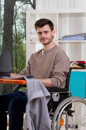Portrait of young disabled man with ironing board photo