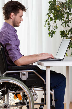 health care worker: Man on wheelchair working on laptop at desk Stock Photo