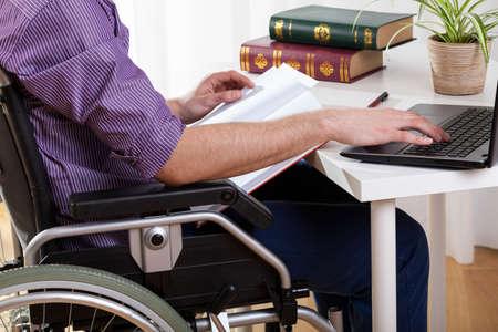 personas discapacitadas: Hombre discapacitado joven que estudia en la mesa en casa