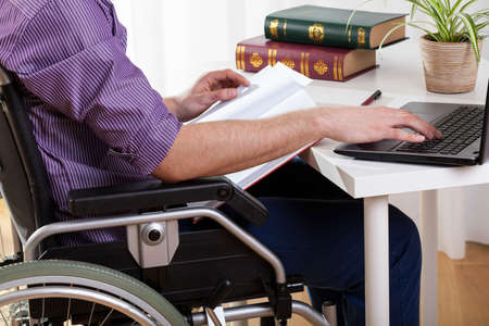 Young disabled man studying at the table at home Stock Photo