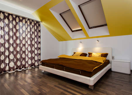 Big bed in modern bedroom in the attic photo