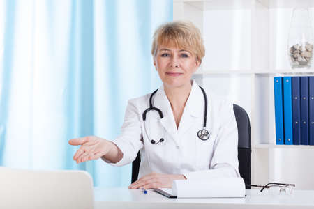 Doctor inviting patient on a chair, horizontal