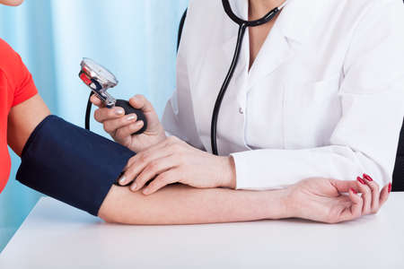 blood pressure monitor: Doctor doing professional pressure examine her young patient Stock Photo