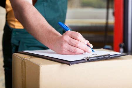 Närbild av en mans hand signering leveransdokument Stockfoto