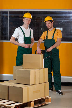 Men with fork pallet truck full of cardboard boxes at warehouse photo