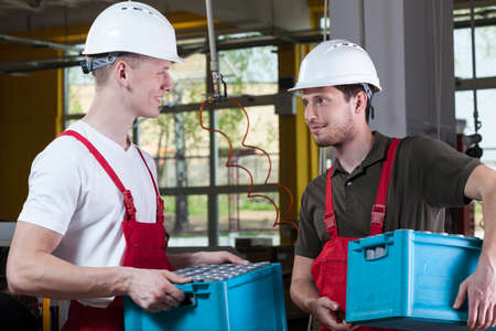 storekeeper: Handsome workers talking in a factory, horizontal Stock Photo