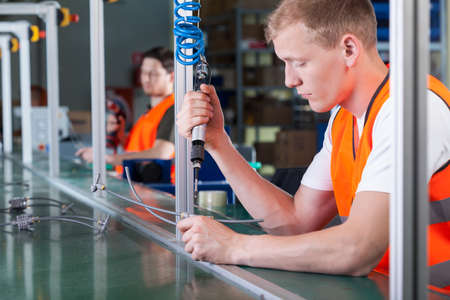 Concentrated young workers on production line, horizontal Stock Photo
