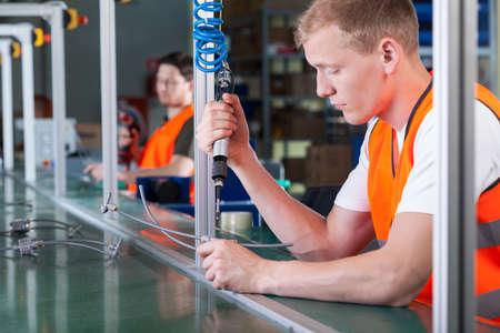 Koncentrované mladí pracovníci na výrobní lince, horizontální Reklamní fotografie