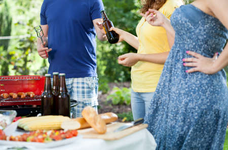 Friends during barbecue in a garden, horizontal photo
