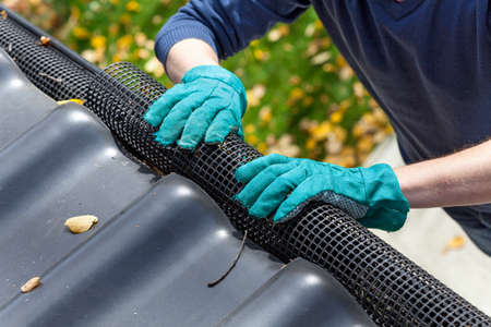 Mans hands in gloves securing gutters with a black net