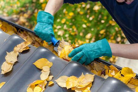 gouttière: Un homme de prendre les feuilles d'automne sur les goutti�res Banque d'images