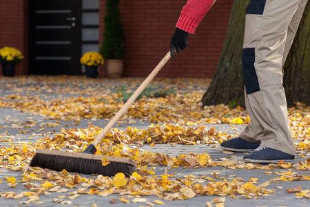 Een man vegen de bladeren van zijn terras