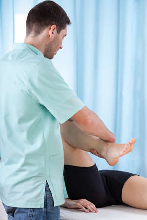 lower limb: Physiotherapist bending knee of patient lying on treatment couch
