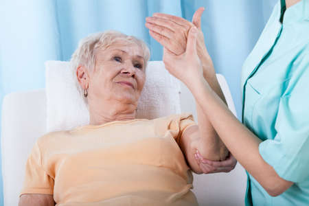 codo: Detalle de senior con el brazo doloroso durante la rehabilitación Foto de archivo
