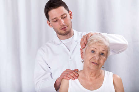 spine surgery: Physiotherapist helping patient with pain of neck Stock Photo