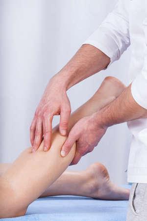 lower limb: Vertical view of masseur massaging tense calf Stock Photo