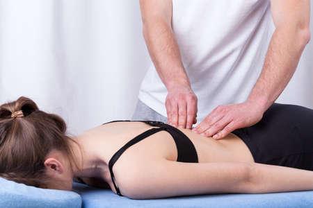 mujeres de espalda: Fisioterapeuta tocar m�sculo tenso de la espalda